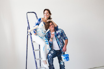 People, redecoration and relationship concept - Young funny couple doing renovation in new apartment
