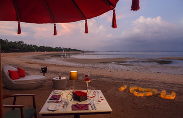 Romantic beach evening dinner during sunset: candles, champagne