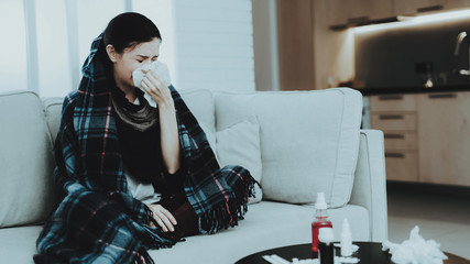 Upset Woman with Cold on Sofa in Scarf at Home.