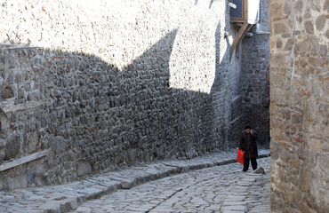Woman walks on a cobblestone street in the Old Town of the city of Plovdiv