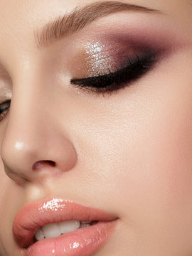 Closeup portrait of young beautiful woman with evening make up. Multicolored smokey eyes. Luxury skincare and modern fashion makeup concept. Studio shot. Extreme closeup, partial face view