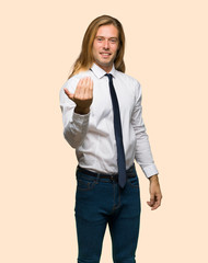 Blond businessman with long hair inviting to come with hand. Happy that you came on isolated background