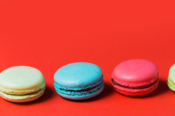 Closeup of French macaroons on red background with copy space