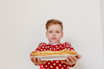 boy in a red shirt holding a plate with pancakes. Pancakes in the foreground. The holiday of Maslenitsa
