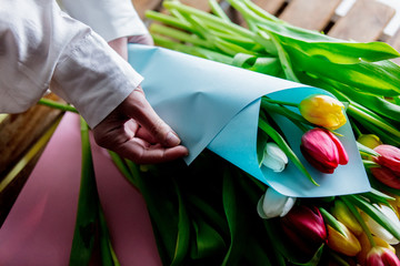 Female hands wrapping beautiful tulips on wooden table