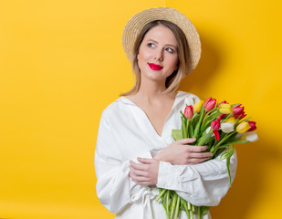 woman in white shirt and hat with fresh springtime tulips