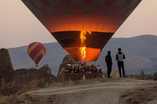 People taking pictures and enjoying balloons at sunrise in Cappadocia, Turkey.