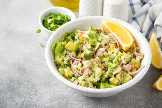 Salad with tuna, avocado, onion, egg and lemon. Spring healthy delicious lunch on light background