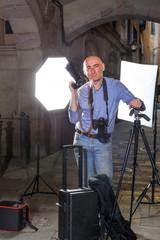 Photographer with camera among photo equipment