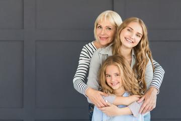 Women hugging, looking at camera and smiling