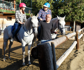 Positive mature couple with  jockey learn to riding horse at farm