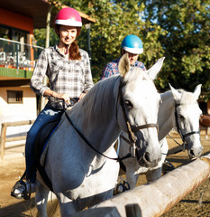 Woman and man in helmets training riding horse at farm at summer day