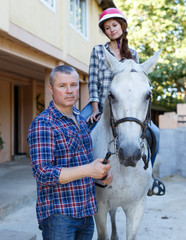 Portrait of man trainer teach to woman while riding horse