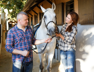 Smiling couple with white horse standing at stable outdoor