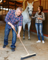 Male worker cleaning floor at stabling, woman farmer standing