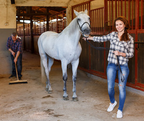 Farmer standing with horse, man cleaning floor at stabling
