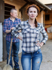 Mature positive family couple with tools standing  at stabling