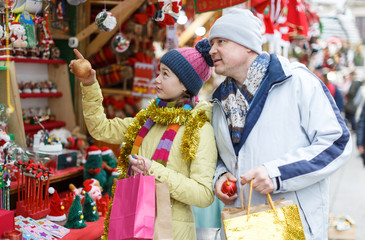 Father with daughter selecting Christmas decoration