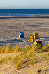 Fototapete - Beach and beach chairs on the East Frisian Island Juist in the North Sea, Germany, in evening light before sunset.