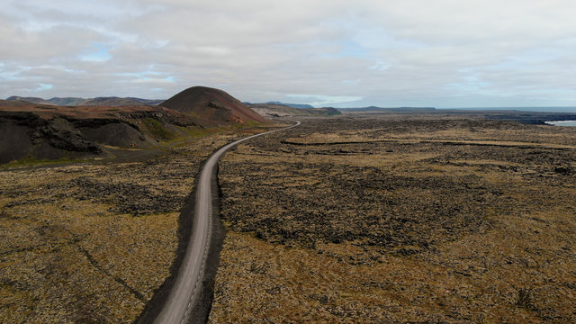 Aerial view of a road cutting through a desolate landscape, Iceland. Panoramic shot created by a drone camera.