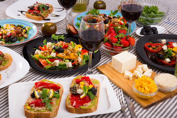 Many plates with different vegetarian food and  glass of wine