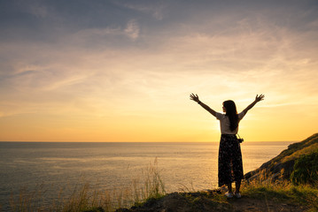 Happy young woman enjoying freedom with open hands and sitting on stone and sunset on the sea sky sunset background