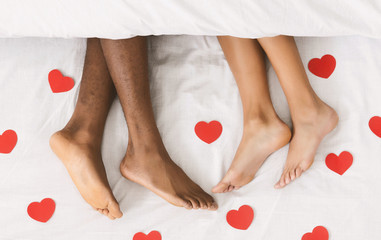 Loving couple legs lying on bed under blanket