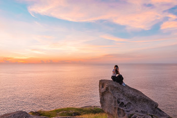 young woman sit on stone and use mobile phone takes a photo with beautiful amazing sea sunset of orange red colors