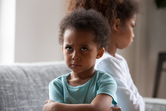 Angry african american little boy offended not talking ignoring black sister after fight, jealous kid brother sulking avoiding preschool girl, siblings bad relationships, two children conflict