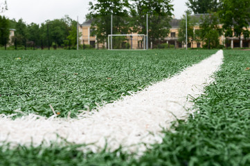 Artificial turf for football game, white line on corner on foreground, nobody