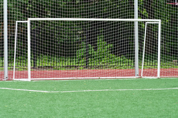 Goalmouth on artificial green playing field, net after white goal