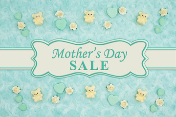 Mother's Day Sale message with teal candy hearts, teddy bears and rose buds on a teal plush fabric with ribbon