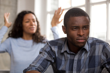 Thoughtful upset african husband feels disappointed in love ignoring avoiding angry wife shouting blaming spouse, sad pensive black man frustrated about couple fight quarrel and bad relationships