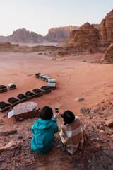 Travelling in Wadi Rum desert, Jordan. Taking photo by smartphone on cliff