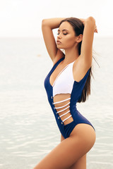 beautiful girl with dark hair in elegant swimming suit relaxing on the summer beach