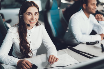 Smiling female operator sitting on dispatch board