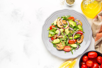 Fresh spring salad with mushrooms, cherry tomatoes, avocado and onions. Tasty vegetarian lunch, healthy food
