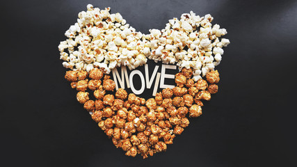 Popcorn on black background. Watching a movie with popcorn. Copy space