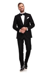 smiling businessman holding hands together and walking