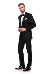 young businessman unbuttoning his black suit while standingyoung businessman unbuttoning his black suit while standing