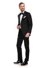handsome businessman in black suit looks to side while standing
