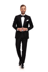 young businessman buttoning his black suit while stepping forward