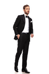 curious businessman in black suit looks to side while walking