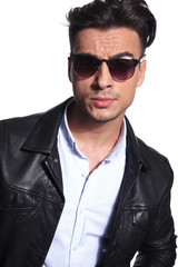attractive smart casual man in leather jacket wearing red sunglasses