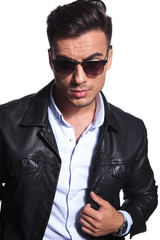 portrait of fashion man in leather jacket and red sunglasses