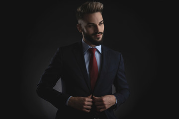 portrait of curious businessman buttoning suit while standing