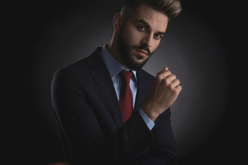 portrait of attractive businessman with beard wearing navy suit