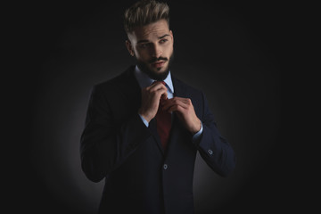 portrait of businessman arranging red tie and looking to side