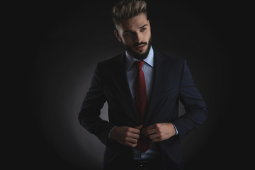 portrait of young attractive businessman buttoning suit