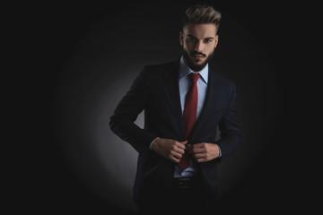 portrait of attractive businessman unbuttoning navy suit